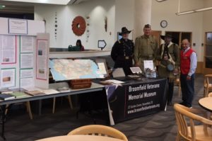 Museum exhibit booth with veterans at local college fair