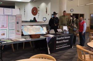 Museum exhibit booth with veterans at local college fair